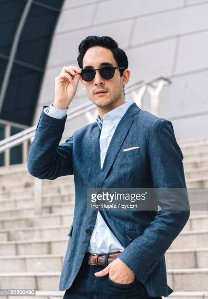 portrait of well-dressed businessman wearing sunglasses in city - menswear stock pictures, royalty-free photos & images