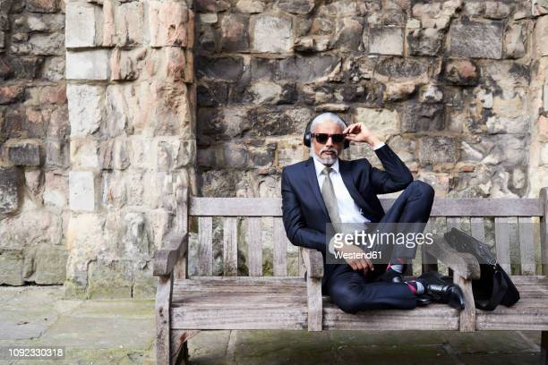 portrait of well-dressed senior businessman with sunglasses and headphones sitting on bench - geschäftskleidung stock-fotos und bilder