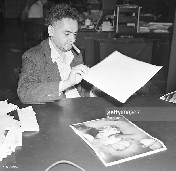 """Portrait of well-known New York freelance photographer Arthur """"Weegee"""" Fellig, seated at his desk examining photos, with a cigar in his mouth. Photo..."""