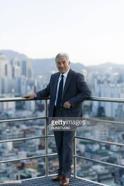 portrait of wenior businessman standing on rooftop - arbeitende rentner stock-fotos und bilder