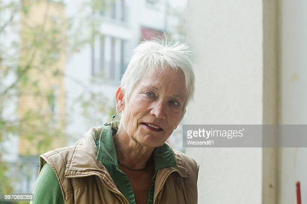 Portrait of white haired senior woman in front of a window