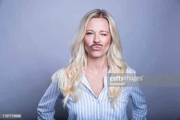 portrait of winking blond woman with fake moustache and hat pouting mouth - 顔の毛 ストックフォトと画像