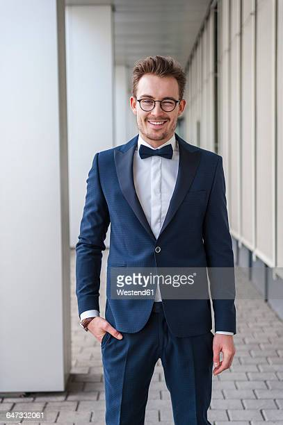 portrait of winking young man wearing suit and bow tie - bow tie stock pictures, royalty-free photos & images