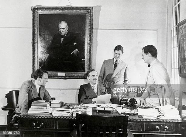 A portrait of Winston Churchill dominates a meeting at which Minister Sir John Balfour talsk with second Secretary N J Henderson Head of the Chancery...