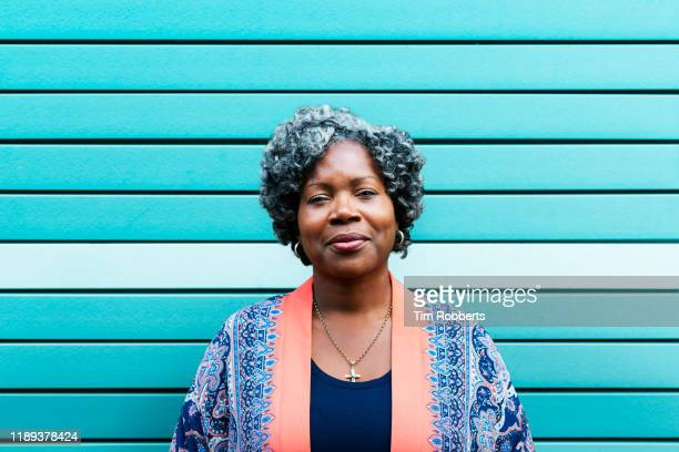 portrait of woman against blue wall - serious stock pictures, royalty-free photos & images