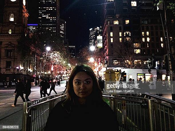 Portrait Of Woman Against Buildings In City At Night