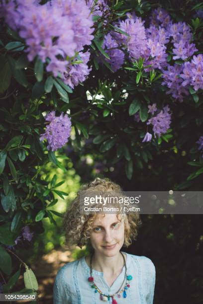Portrait Of Woman Against Purple Flowering Plants
