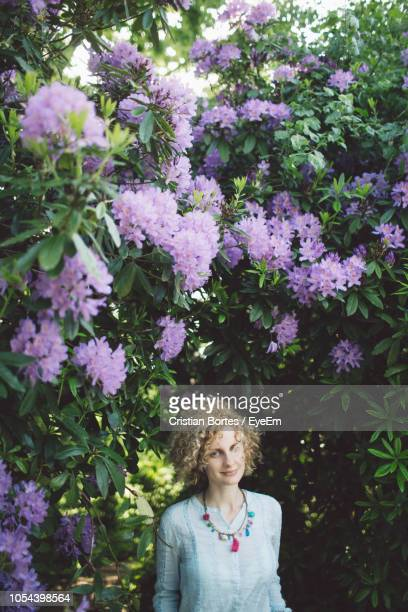 portrait of woman against purple flowering plants - bortes stock-fotos und bilder