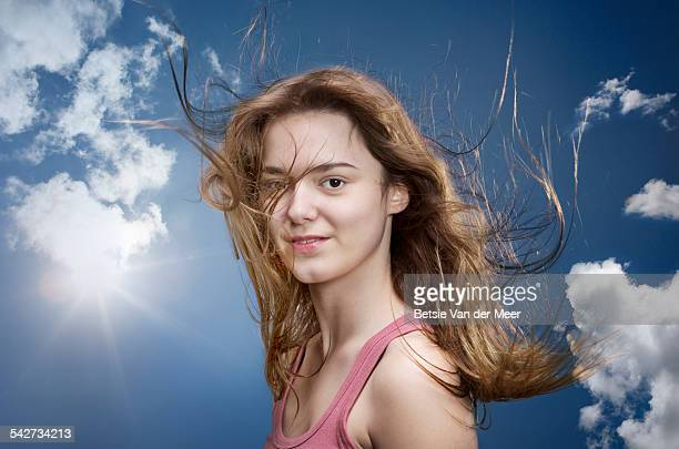 Portrait of woman against sky, windswept hair.
