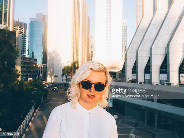 portrait of woman against skyscrapers in tel aviv - israeli woman stock pictures, royalty-free photos & images