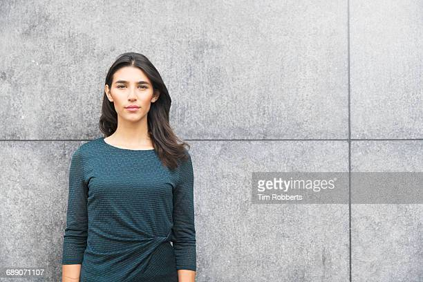 portrait of woman against wall - green dress stock pictures, royalty-free photos & images