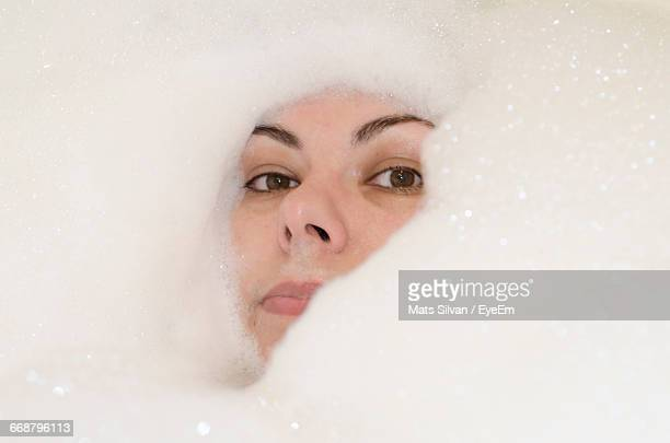Portrait Of Woman Amidst Soap Sud In Bathtub