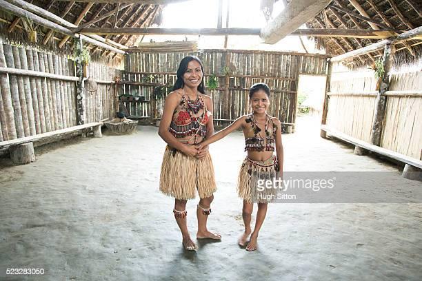 portrait of woman and girl (8-9) in traditional hut, amazon river basin, ecuador - hugh sitton stock-fotos und bilder