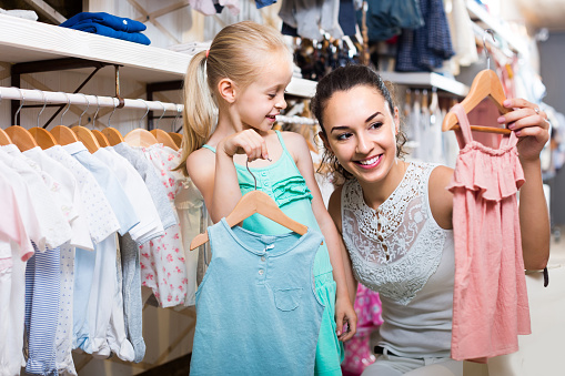 portrait of  woman and girl shopping kids apparel in clothes store 1081340474