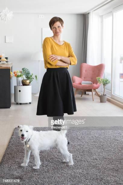 portrait of woman and her dog in the living room - alleen één mid volwassen vrouw stockfoto's en -beelden