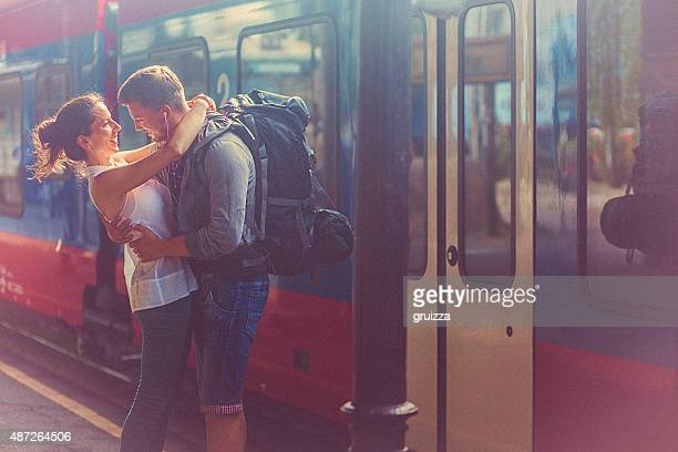 Portrait of woman and man embracing at the railway platform