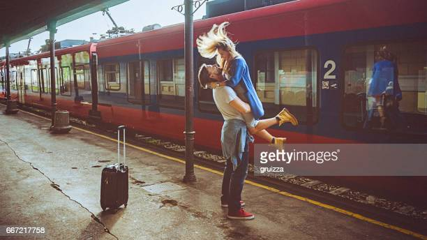 portrait of woman and man embracing at the railway platform - estação imagens e fotografias de stock