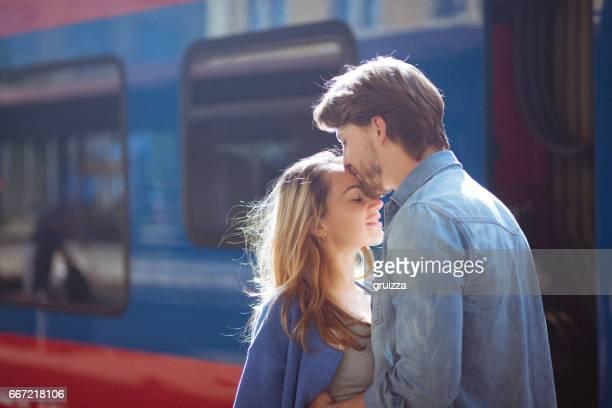 Porträtt av kvinna och man som omfamnar vid järnvägen plattformen