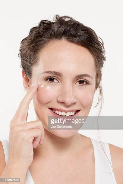 Portrait of woman applying face cream, studio shot