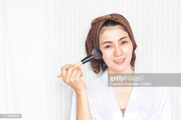 portrait of woman applying make-up against wall - メイクアップブラシ ストックフォトと画像
