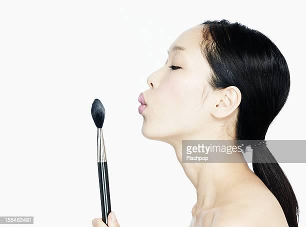 portrait of woman applying make-up with brush - 吹く ストックフォトと画像