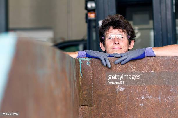 Portrait of woman at a waste container