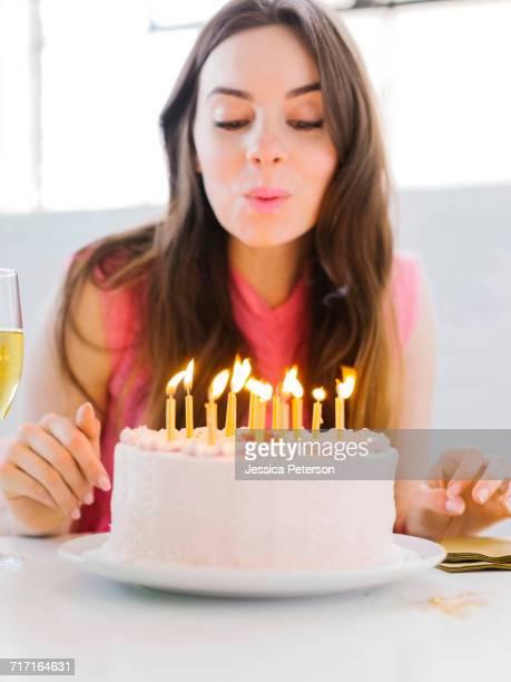 portrait of woman at birthday party - soffiare foto e immagini stock