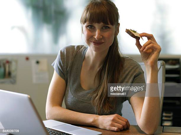Portrait of woman at desk with laptop eating bread