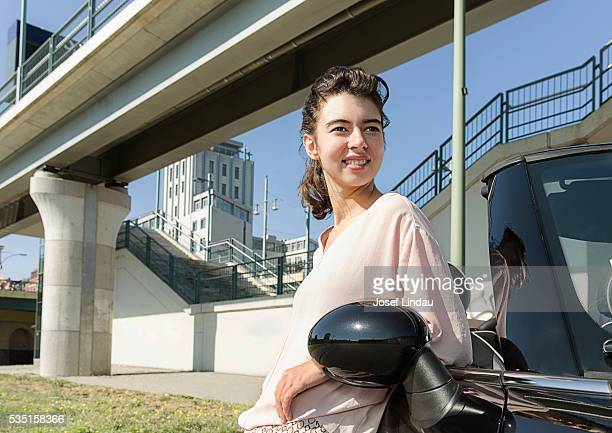 Portrait of woman at side of her open top car
