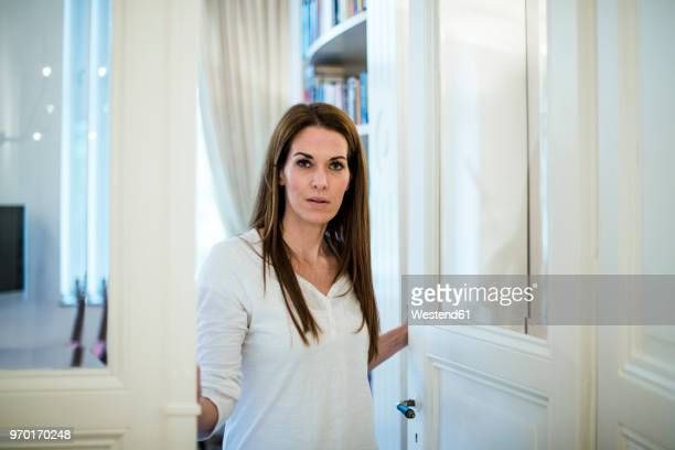 portrait of woman at the door at home - open grave stock photos and pictures