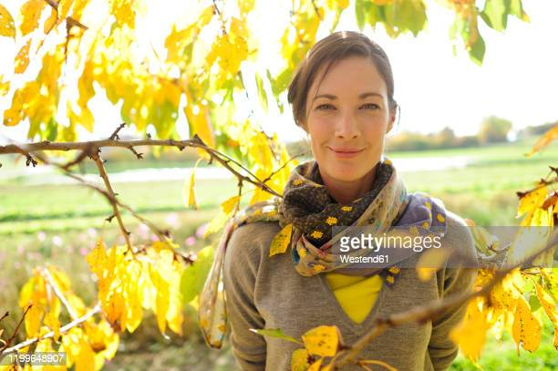 portrait of woman at twigs with autumn leaves looking at camera - one mid adult woman only stock pictures, royalty-free photos & images