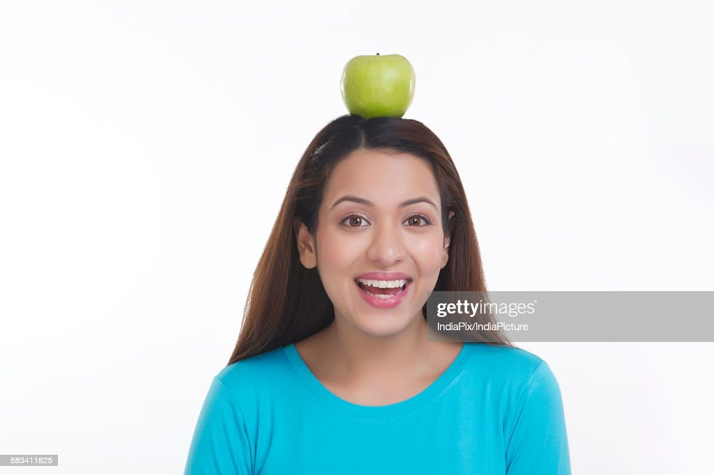 Portrait of woman balancing apple on head : Stock Photo