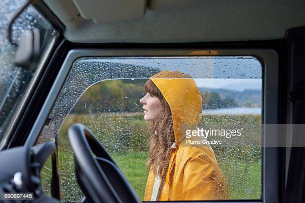 Portrait of woman behind rain covered window