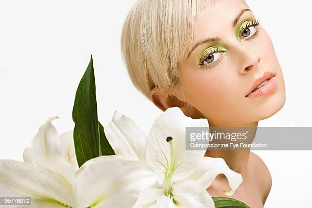 portrait of woman behind white flowers - アイメイク ストックフォトと画像
