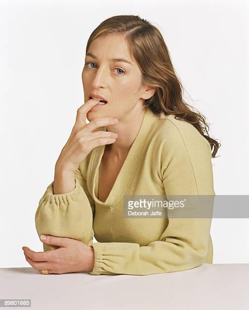 Portrait of woman biting finger
