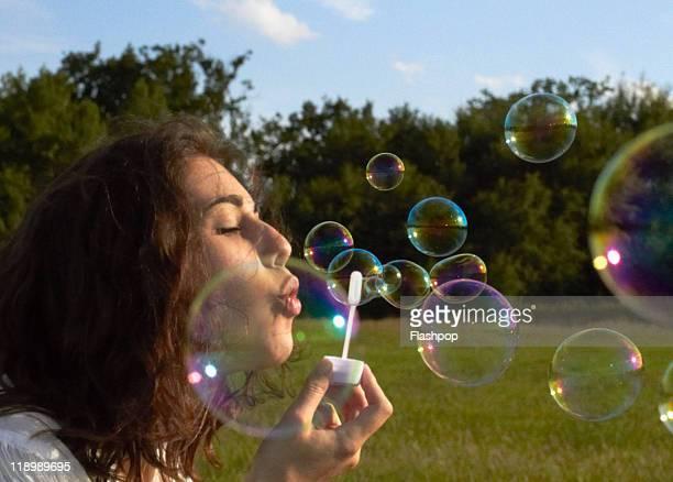 Portrait of woman blowing bubbles