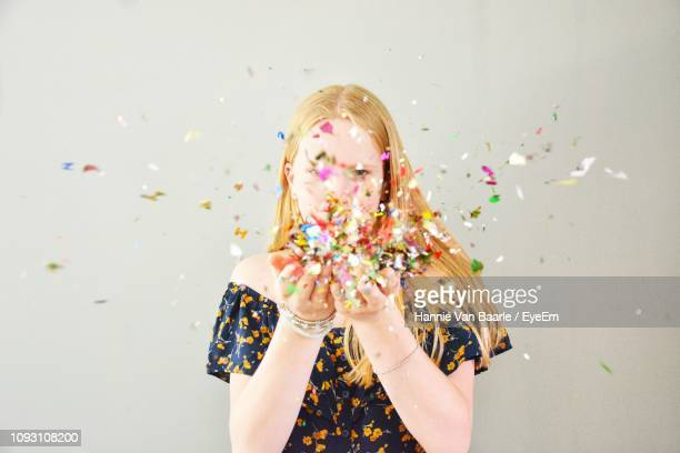 Portrait Of Woman Blowing Confetti Against Gray Background