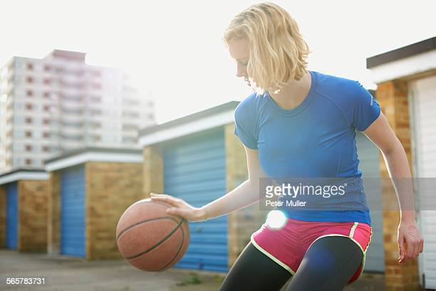 portrait of woman bouncing basketball - one young woman only stock pictures, royalty-free photos & images