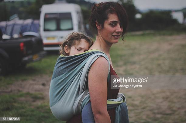Portrait Of Woman Carrying Daughter In Fabric On Field