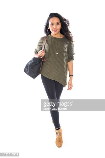 portrait of woman carrying purse while walking against white background - white purse stock pictures, royalty-free photos & images