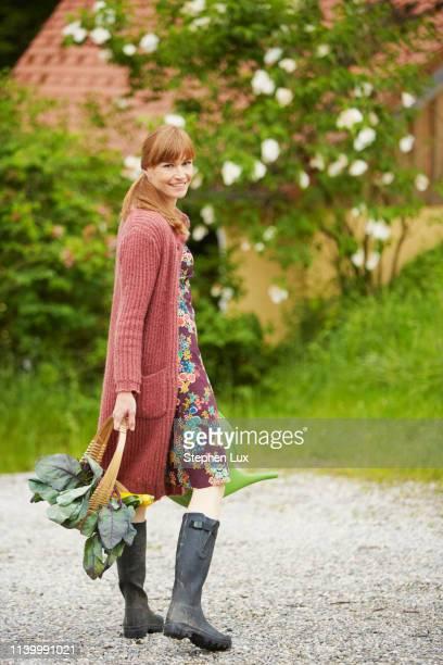 portrait of woman carrying vegetables along rural road - gummistiefel frau stock-fotos und bilder