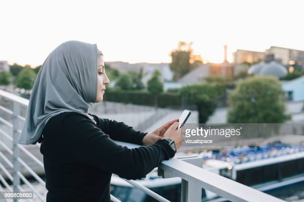 Portrait of woman checking her phone in a sunny evening.