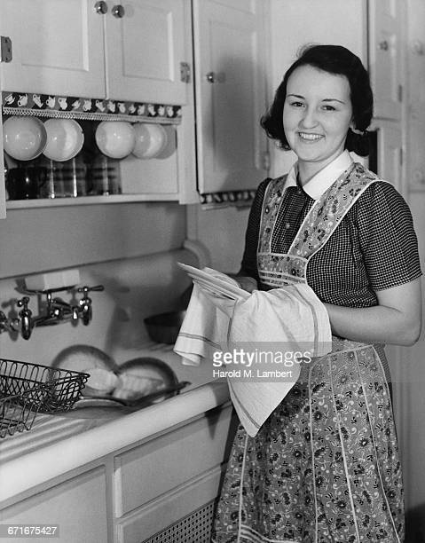 portrait of woman cleaning plates and smiling  - {{ contactusnotification.cta }} stock pictures, royalty-free photos & images