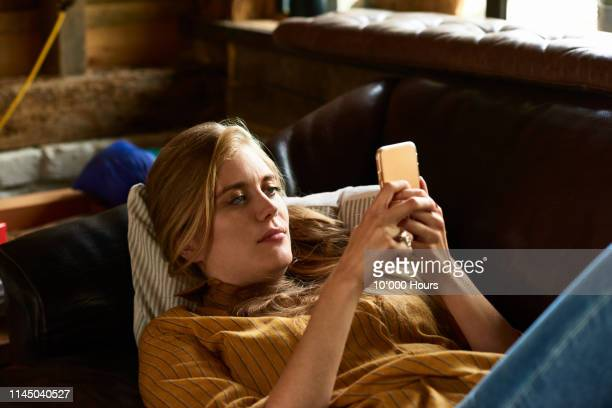 portrait of woman concentrating on phone reclining on couch - candid forum stock pictures, royalty-free photos & images