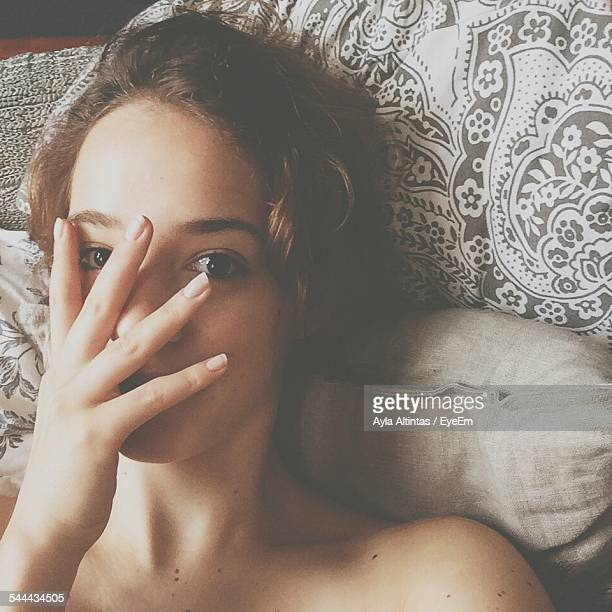 Portrait Of Woman Covering Face With Hand While Relaxing On Bed At Home