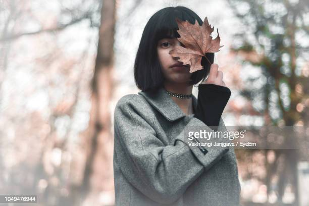 Portrait Of Woman Covering Face With Maple Leaf While Standing On Field
