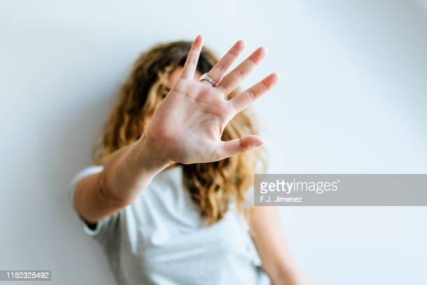 portrait of woman covering her face with her hand - esconder imagens e fotografias de stock