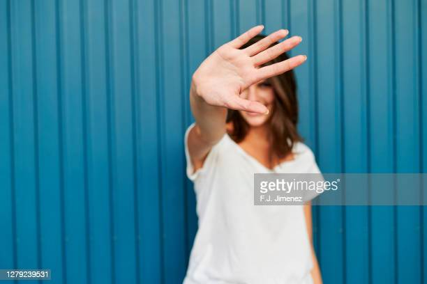 portrait of woman covering her face with her hand - ストップ ストックフォトと画像