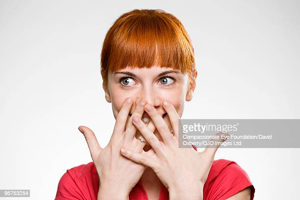 portrait of woman covering her mouth with her hand - surpresa - fotografias e filmes do acervo