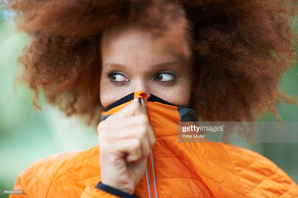 Portrait of woman covering mouth with coat looking away : Foto de stock